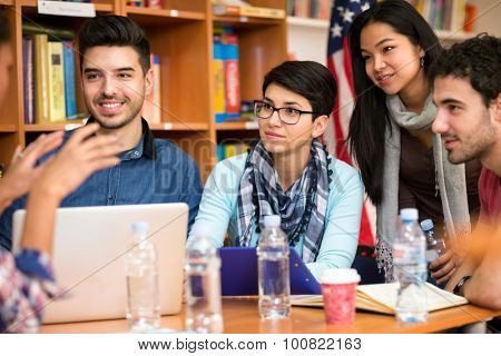 Group of young students discussing about task