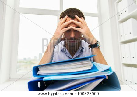 business, people, deadline, stress and paperwork concept - sad businessman with stack of folders at office poster