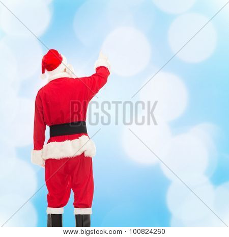 christmas, holidays and people concept - man in costume of santa claus pointing finger from back over blue lights background