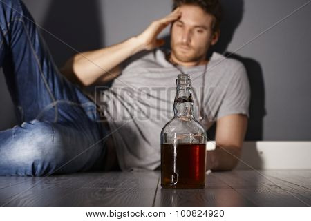 Young addicted man with a bottle of whiskey.