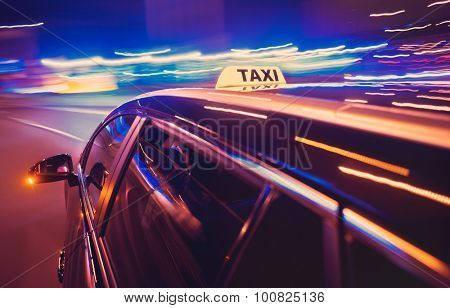 Taxi taking a left turn at night in an urban surrounding, seen from the rear end of the cab