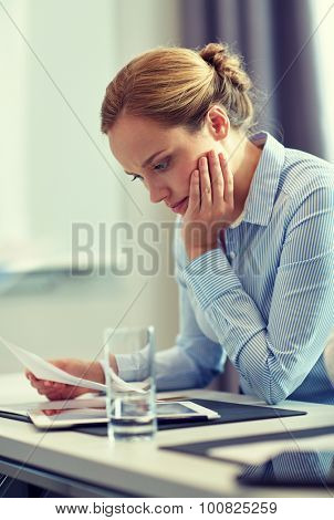 business, people and crisis concept - businesswoman sitting sad and reding document in office