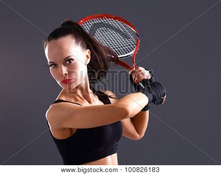 Woman playing tennis on gray background