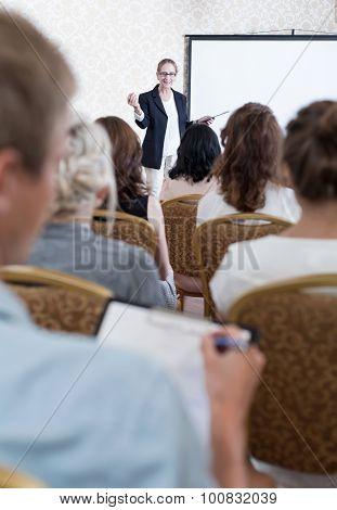 Man Taking Notes During Symposium