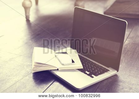 Smartphone On Open Book And Laptop On A Floor, Vintage Photo Effect