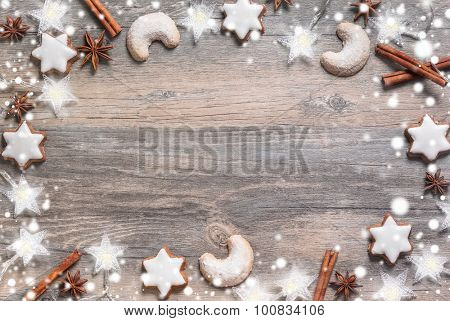 Christmas background with gingerbread cookies,christmas lights and spices on the old wooden board. Image in cool vintage tone