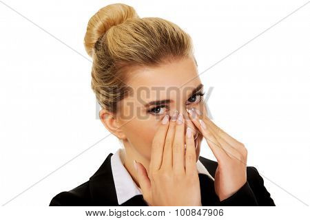 Businesswoman giggles covering her mouth with hand.