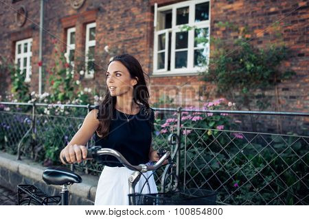 Woman With Bike Walking Along The Road