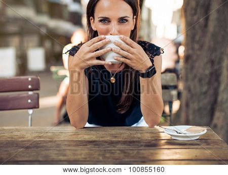 Young Woman Drinking Coffee At A Cafe