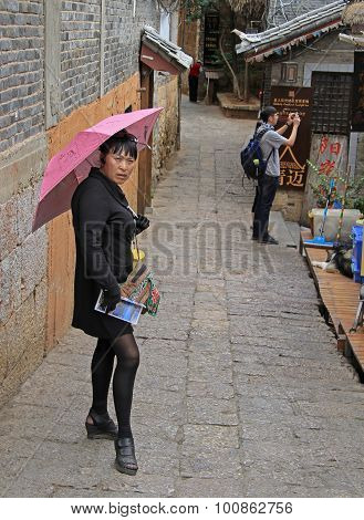 woman with pink umbrella is waiting someone on the street in Lijiang, China