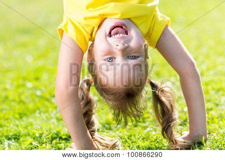 Happy child has fun standing head down on green grass