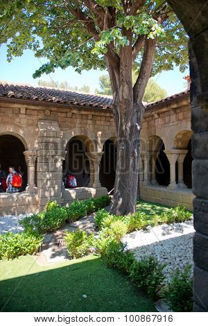BARCELONA, SPAIN - MAY 02: Inner courtyard with trees and a garden surrounded by an arched colonnade with a tourist visible walking through in Espanyol Poble, Barcelona, Spain. May 02, 2015.