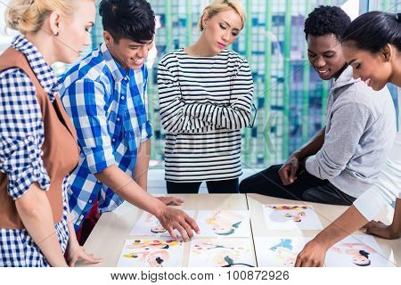 Advertising agency team choosing key visual among pictures spread out on the table