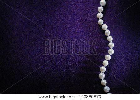 pearl beads on purple velvet background