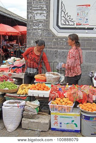 women are selling fruits on the market in Lijiang