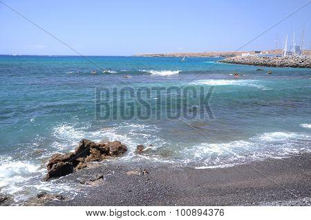 Picturesque black pebble beach in Las Galletas on the south of Tenerife, Spain