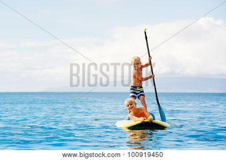 Young Boys Having Fun Stand Up Paddling Together in the Ocean
