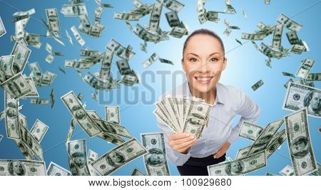 business, money, finance, people and banking concept - smiling businesswoman with heap of dollar cash money over blue background