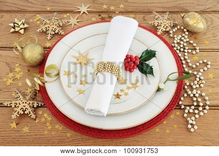 Christmas dinner place setting with plates, napkin, holly and mistletoe with gold stars and baubles over oak background.