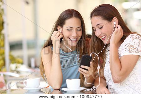 Friends Sharing And Listening To Music With Smartphone