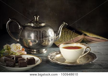 Tea In A Porcelain Cup, Old Fashioned Silver Teapot, Chocolate Cookies And A Good Book On Rustic Woo