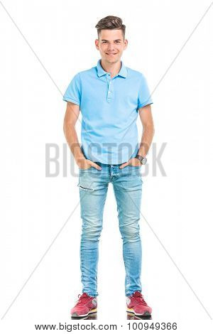 Full length picture of a young casual man holding his hands in pockets while standing on isolatd background.