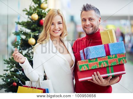 Cheerful shoppers with paperbags and giftboxes looking at camera