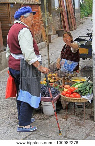 woman-seller of vegetables is talking with her friend on the street in Lijiang, China