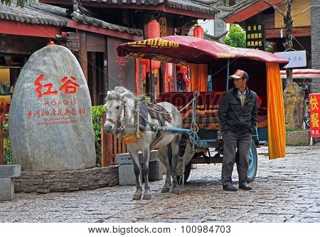 coachman of horse-drawn vehicle is waiting customers on the street in Lijiang, China