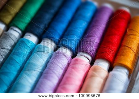 Colored sewing threads. Focus on purple thread. Shallow depth of field.