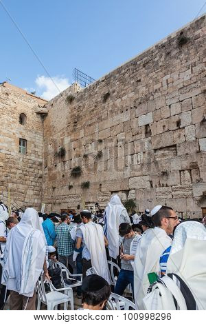 JERUSALEM, ISRAEL - OCTOBER 12, 2014: The area in front of Western Wall of  Temple filled with people. Crowd of faithful Jews wearing prayer shawls. Morning autumn Sukkot