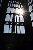 Silhouetted arched window with the sun bursting through within the ruins of the old Cathedral Coventry West Midlands England UK Western Europe. poster