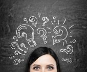 A forehead of the brunette girl who is pondering about unsolved problems. Question marks are drawn around the head. black chalkboard background. poster