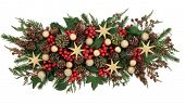 Christmas floral display with star and gold baubles, holly, mistletoe, ivy and winter greenery over white background. poster