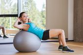 fitness, sport, training and people concept - smiling woman flexing abdominal muscles with exercise ball in gym poster