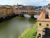 Florence Italy houses and shops in the ancient bridge called Ponte Vecchio over River Arno poster