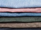 stack of various jeans and corduroy slacks close up poster