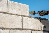 orker make concrete wall by cement block and plaster at construction site worker hand wearing glove laying block to making wall poster