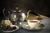 good old tea time black tea in a porcelain cup old-fashioned silver teapot chocolate cookies and a good book on a rustic wooden table copy space in the dark brown background poster