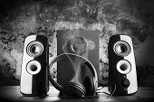 Modern black sound speakers and headphones smoking from overload poster