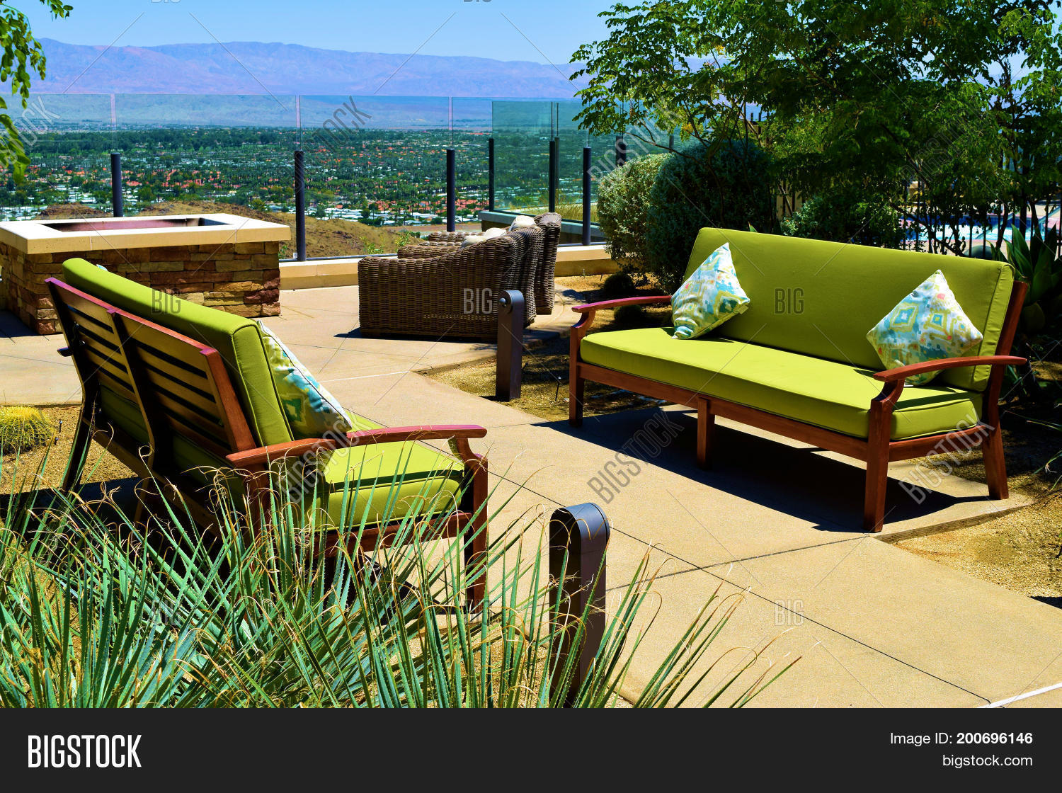 Contemporary style outdoor patio furniture including comfortable sofas with pillows at a residential garden overlooking the