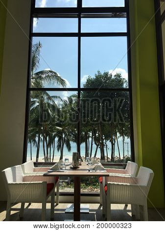 Set table and white chairs in front of a window with beach and sea view
