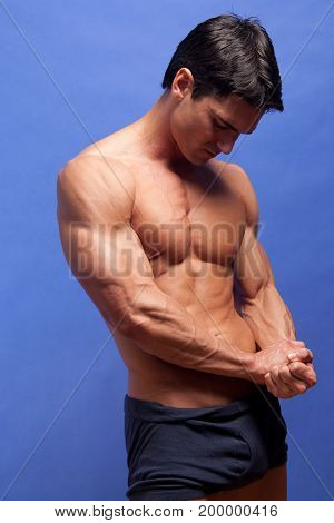 The handsome warrior flexes his muscles shirtless.
