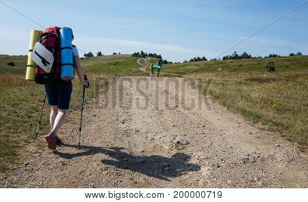 Young girl tourist with backpack walking along a mountain road