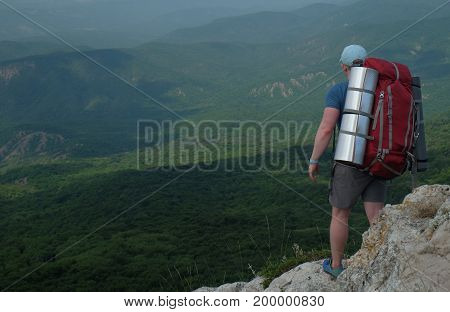 Young man tourist with a big backpack standing on the edge of a precipice and looking at mountain landscape