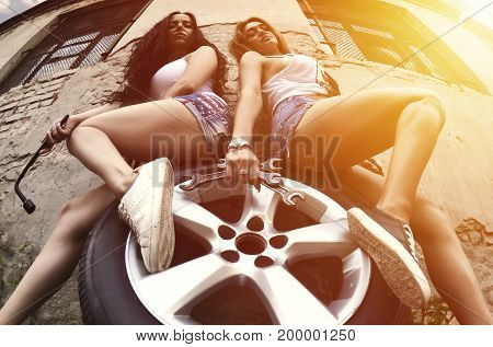 Two Young And Sexy Girls With Wrenches Are Sitting On The Car Wheel
