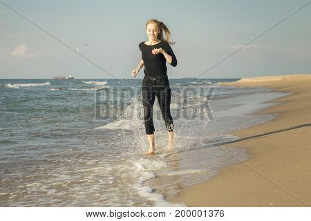 happy blond woman running at sunny sea beach smiling