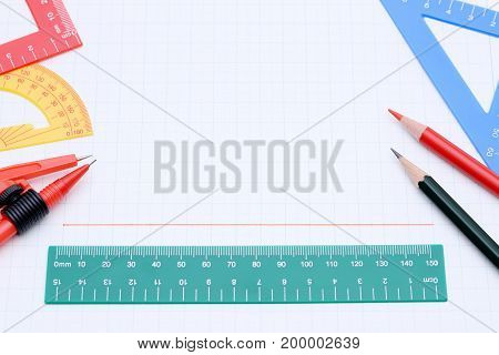 Multicolored rulers, pen and notebook on white background