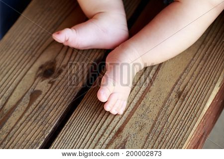 Little naked baby's legs on the bench