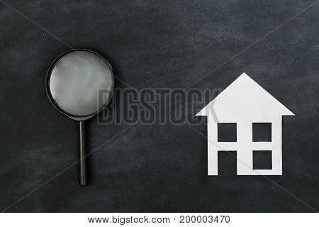 High Angle View Of Magnifier With Paper House
